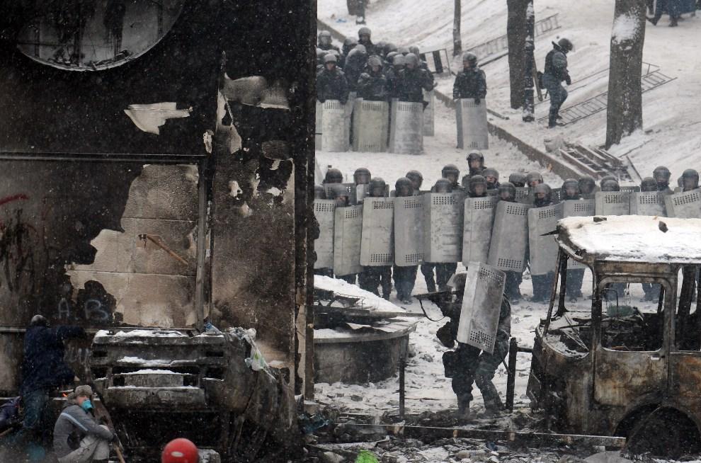 11.UKRAINA, Kijów, 22 stycznia 2014: Protestujący chronią się przed ostrzałem za wrakiem samochodu. AFP PHOTO/ VASILY MAXIMOV