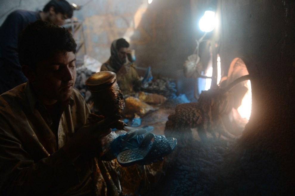 11.AFGANISTAN, Kabul, 15 stycznia 2014: Mężczyźni lakierują buty zrobione z przetworzonego plastiku. AFP PHOTO/SHAH Marai