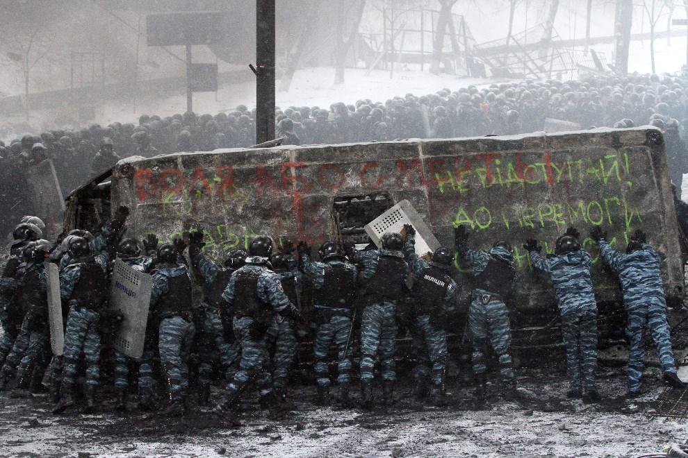 12.UKRAINA, Kijów, 22 stycznia 2014: Milicjanci przewracają swoją furgonetkę spaloną w trakcie walk. AFP PHOTO/ ANATOLII BOIKO