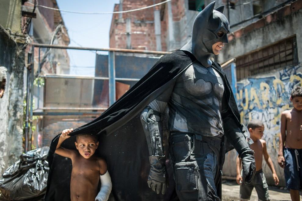 13.BRAZLIA, Rio de Janeiro, 9 stycznia 2014: Chłopiec mieszkający w faweli chowa się pod płaszcz mężczyzny w kostiumie Batmana. AFP PHOTO / YASUYOSHI CHIBA