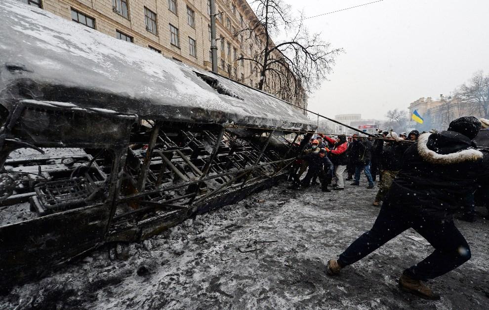 13.UKRAINA, Kijów, 22 stycznia 2014: Opozycjoniści budują barykadę ze spalonego autobusu. AFP PHOTO / VASILY MAXIMOV