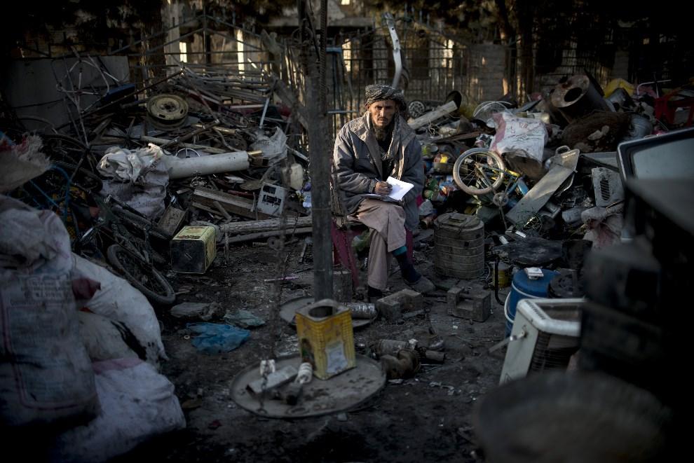 14.AFGANISTAN, Kabul, 17 stycznia 2014: Pracownik skupu złomu w swoim miejscu pracy. AFP PHOTO / JOHANNES EISELE