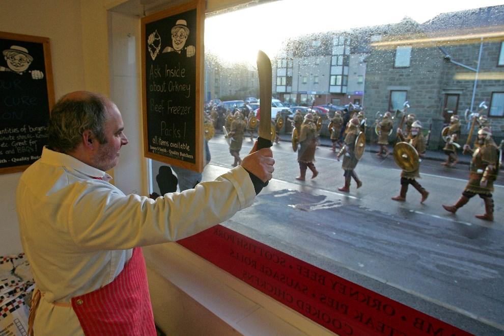 15.WIELKA BRYTANIA, Lerwick, 29 stycznia 2008: Rzeźnik pozdrawia wikingów maszerujących ulicą. AFP PHOTO/CARL DE SOUZA