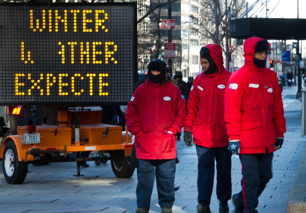 15.USA, Nowy Jork, 7 stycznia 2014: Pracownicy służb miejskich na tle tablicy informującej o niskich temperaturach. AFP PHOTO/MLADEN ANTONOV