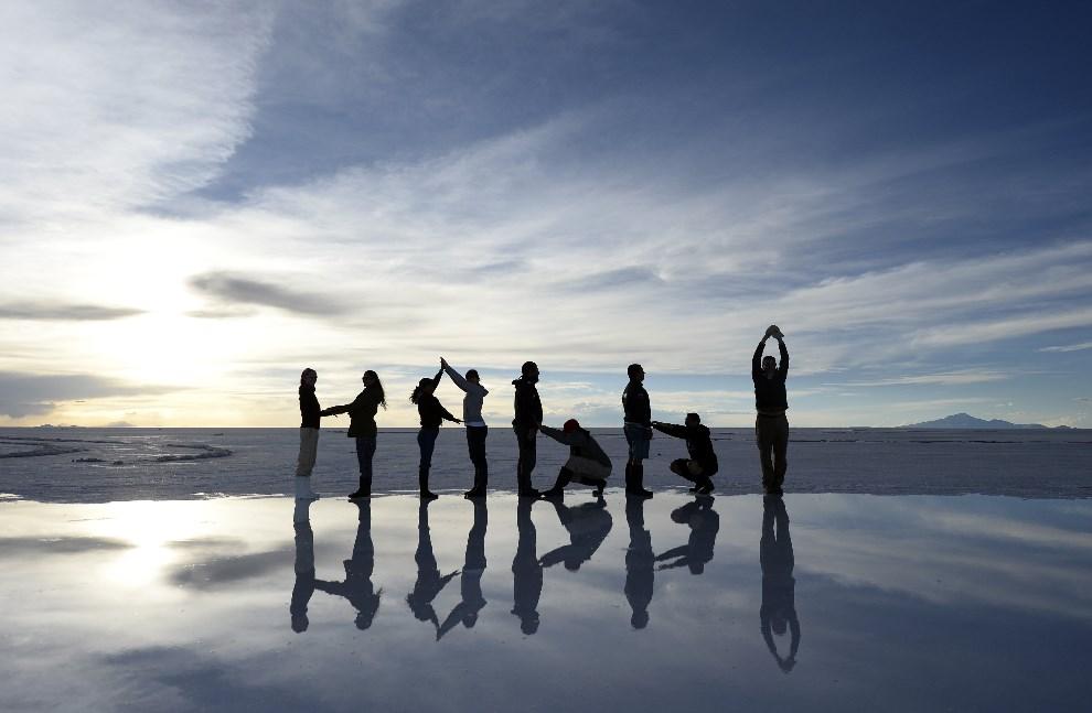 16.BOLIWIA, Uyuni, 11 stycznia 2014: Turyści pozują do zdjęcia na solnisku Salar de Uyuni. AFP PHOTO / FRANCK FIFE
