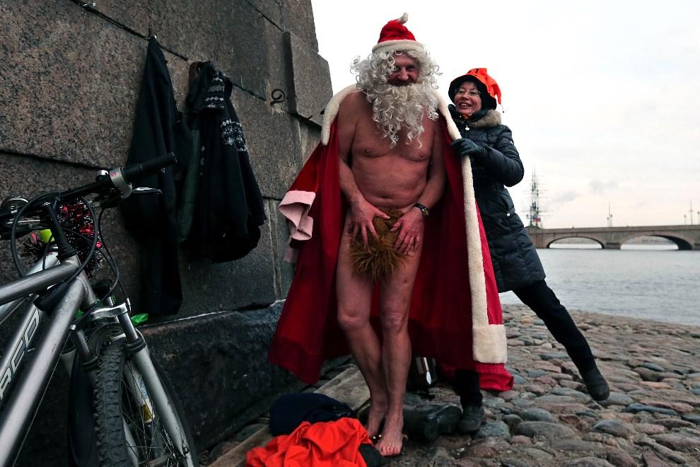 16.ROSJA, Petersburg, 12 stycznia 2014: Mężczyzna w stroju Mikołaja przygotowuje się do kąpieli w Newie. AFP PHOTO/OLGA MALTSEVA