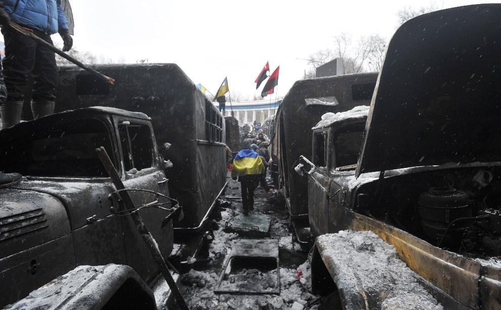 16.UKRAINA, Kijów, 21 stycznia 2014: Protestujący między spalonymi ciężarówkami. AFP PHOTO/GENYA SAVILOV