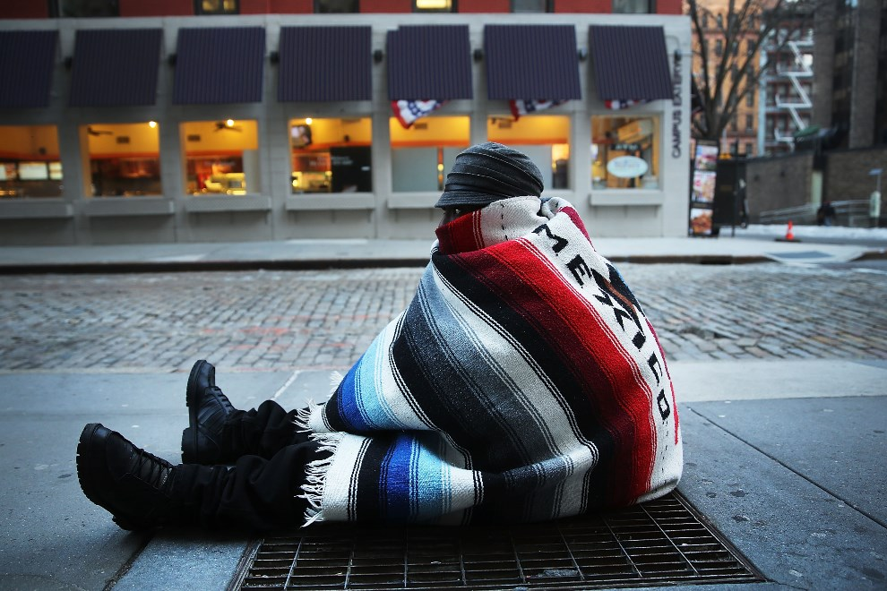 16.USA, Nowy Jork, 7 stycznia 2014: Bezdomny mężczyzna siedzi na kracie wentylacyjnej jednej ze stacji metra. (Foto: Spencer Platt/Getty Images)