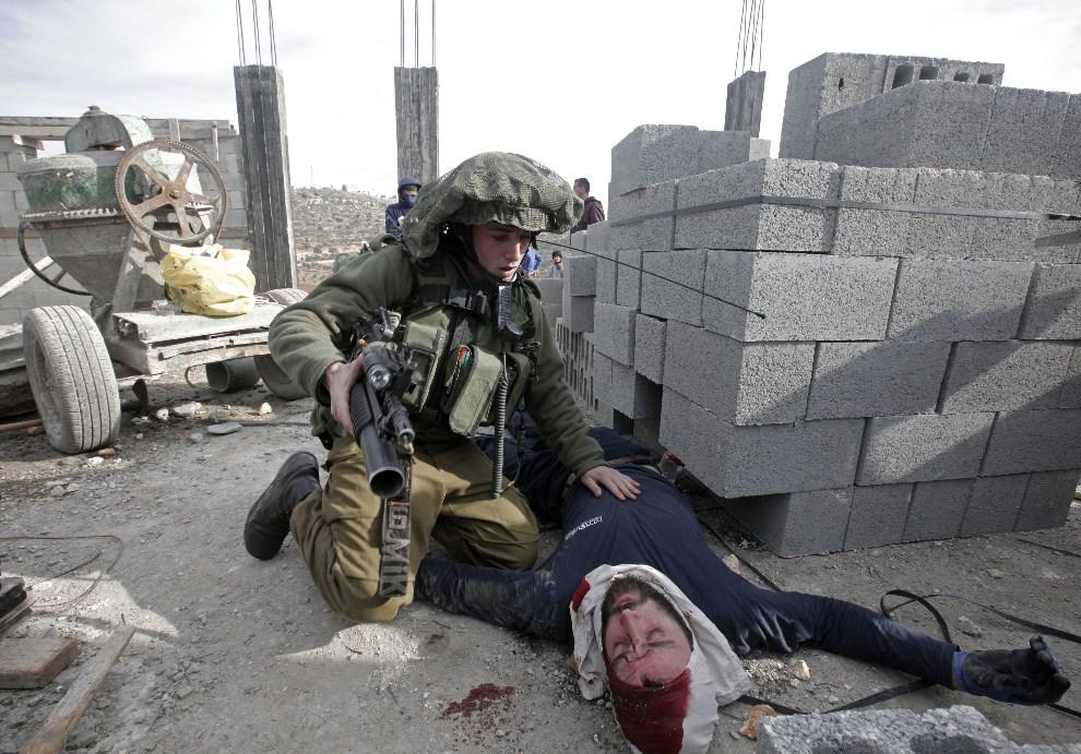 18.PALESTYNA, Qusra, 7 stycznia 2014: Izraelski żołnierz udziela pomocy osadnikowi pobitemu przez Palestyńczyków. AFP PHOTO /JAAFAR ASHTIYEH