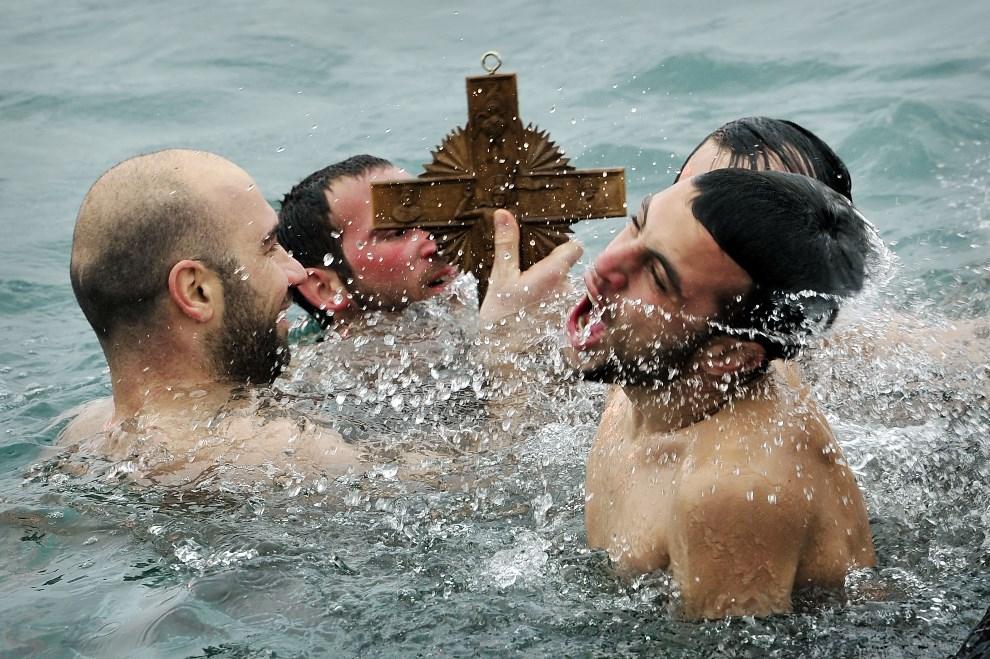 19.GRECJA, Aegina, 6 stycznia 2014: Mężczyźni wyławiają krzyż wrzucony do morza w porcie Aegina. AFP PHOTO / LOUISA GOULIAMAKI