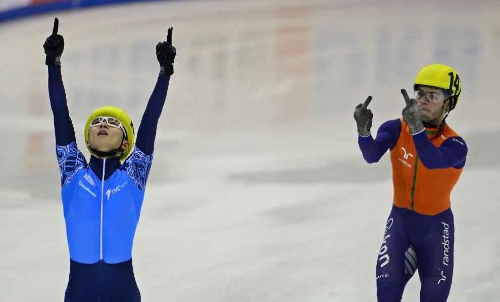 20.NIEMCY, Drezno, 19 stycznia 2014: Holender Sjinkie Knegt (po prawej) i Victor An (po lewej, Rosja) po przejechaniu linii mety wyścigu na dystansie 5000m. AFP PHOTO / ROBERT MICHAEL