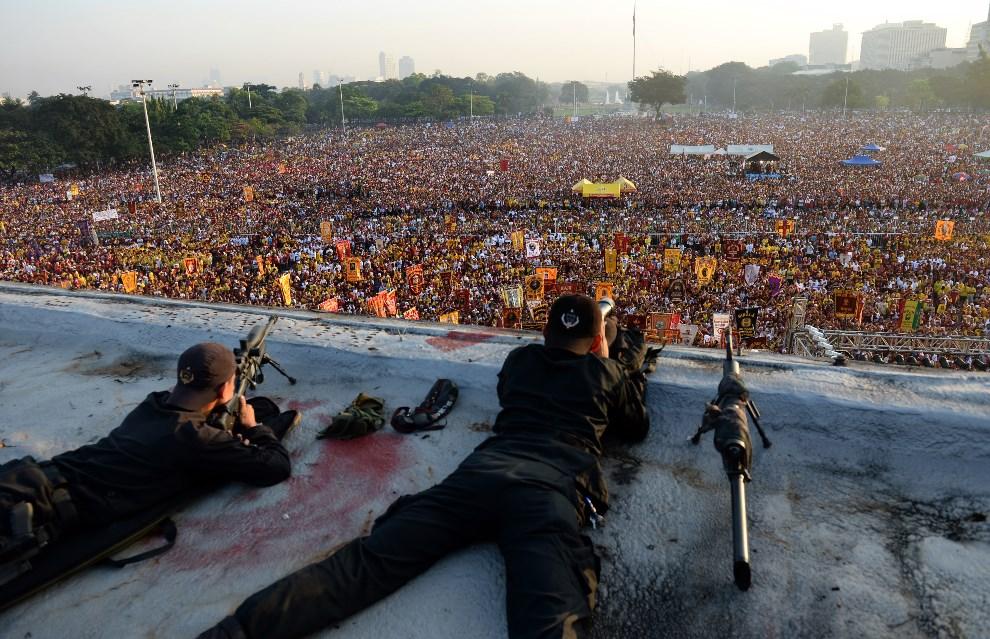 19.FILIPINY, Manila, 9 stycznia 2014: Policyjni snajperzy obserwują wiernych podczas procesji, w obawie przed atakiem terrorystycznym. AFP PHOTO / TED ALJIBE