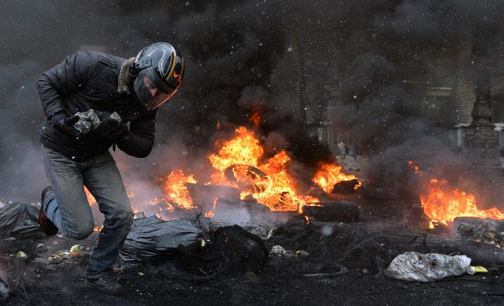 19.UKRAINA, Kijów, 22 stycznia 2014: Mężczyzna przygotowuje się do rzucania kamieni w kierunku milicjantów. AFP PHOTO / SERGEI SUPINSKY