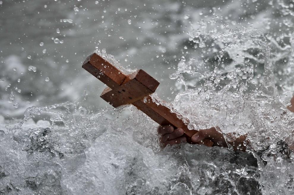 20.GRECJA, Ateny, 6 stycznia 2014: Mężczyzna z krzyżem w trakcie błogosławieństwa. AFP PHOTO / ARIS MESSINIS