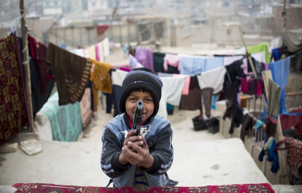 1.AFGANISTAN, Kabul, 16 stycznia 2014: Dziewięcioletni Zubair Ahmad bawi się plastikowym pistoletem. AFP PHOTO/JOHANNES EISELE