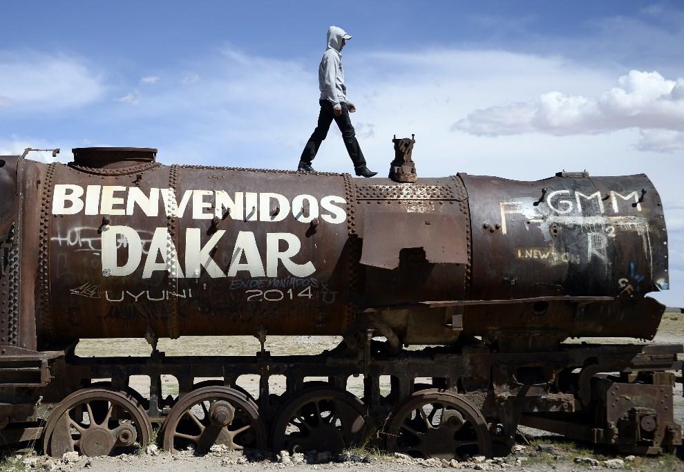 1.BOLIWIA, Uyuni, 11 stycznia 2014: Turysta na złomowanej lokomotywie. AFP PHOTO / FRANCK FIFE
