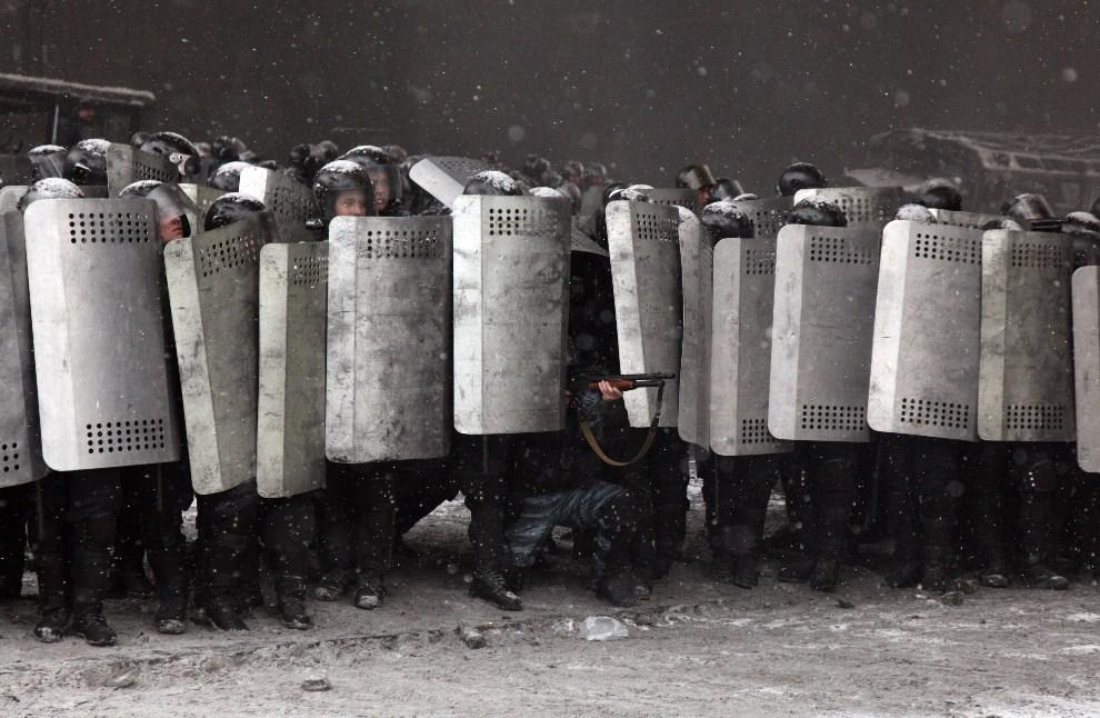 1.UKRAINA, Kijów, 22 stycznia 2014: Milicjant mierzy z broni w kierunku protestujących. AFP PHOTO / ANATOLIY STEPANOV