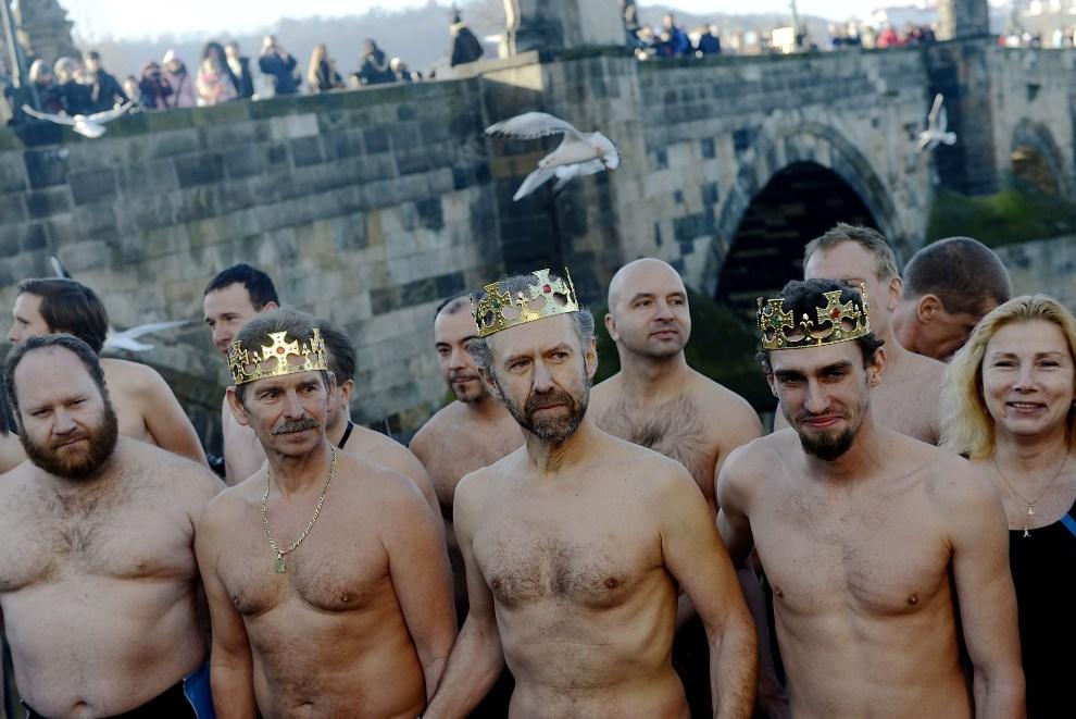 1.CZECHY, Praga, 6 stycznia 2014: Mężczyźni na tle mostu Karola przygotowują się do kąpieli w Wełtawie.  EPA/FILIP SINGER Dostawca: PAP/EPA.