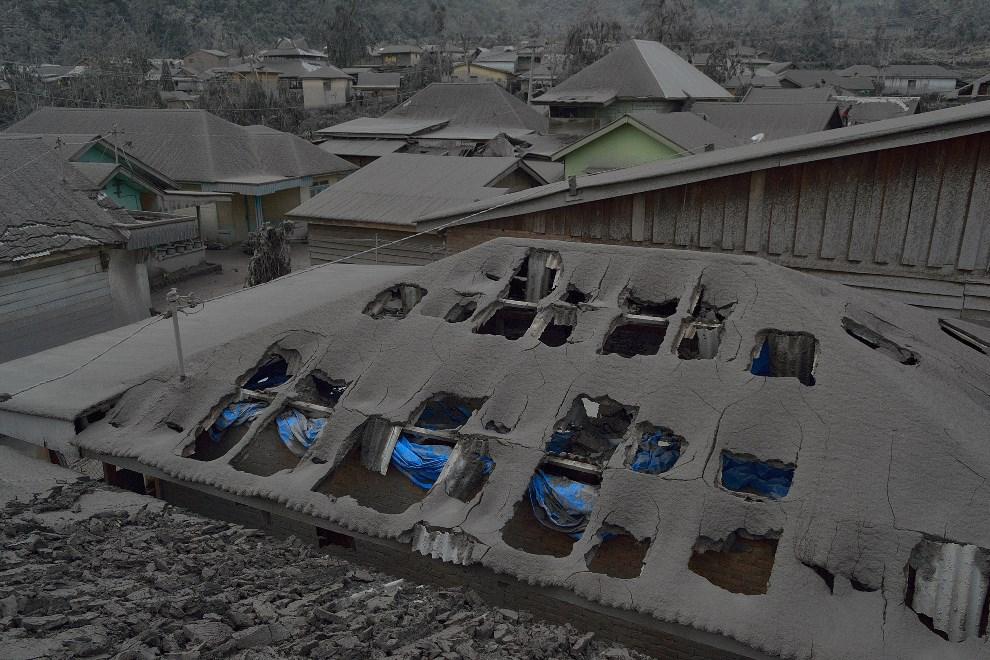 20.INDONEZJA, Karo, 12 stycznia 2014: Dachy domów przykryte pyłem wulkanicznym. AFP PHOTO / Sutanta ADITYA