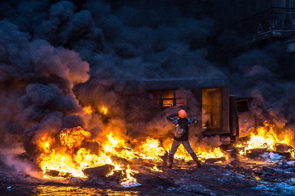 21.UKRAINA, Kijów, 22 stycznia 2014: Protestujący na tle płonącej barykady. AFP PHOTO/ DMITRY SEREBRYAKOV