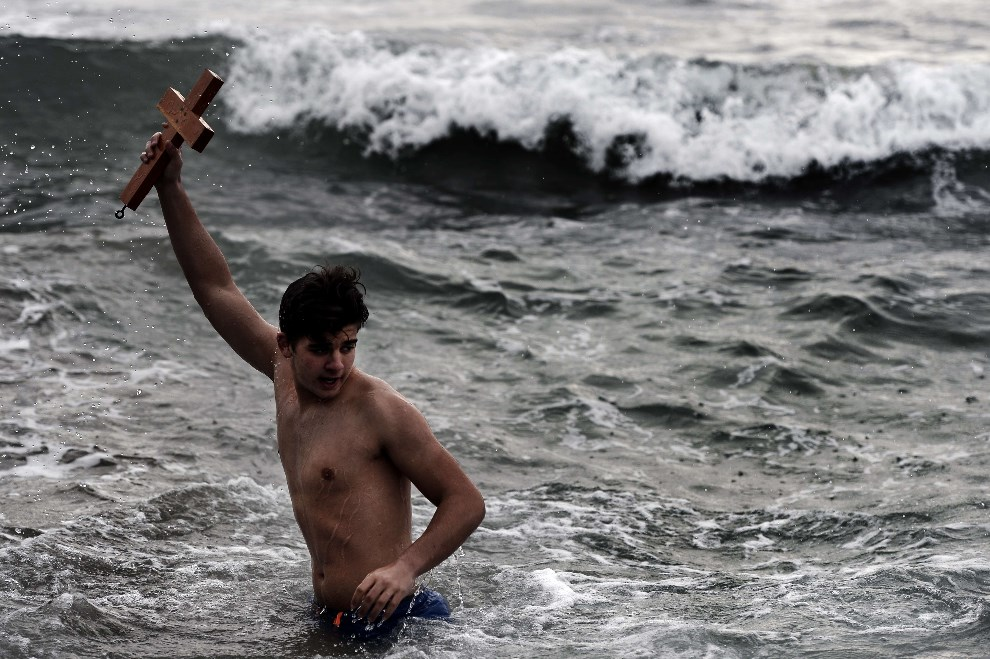 22.GRECJA, Ateny, 6 stycznia 2014: Mężczyzna trzyma wyłowiony z morza krzyż. AFP PHOTO / ARIS MESSINIS