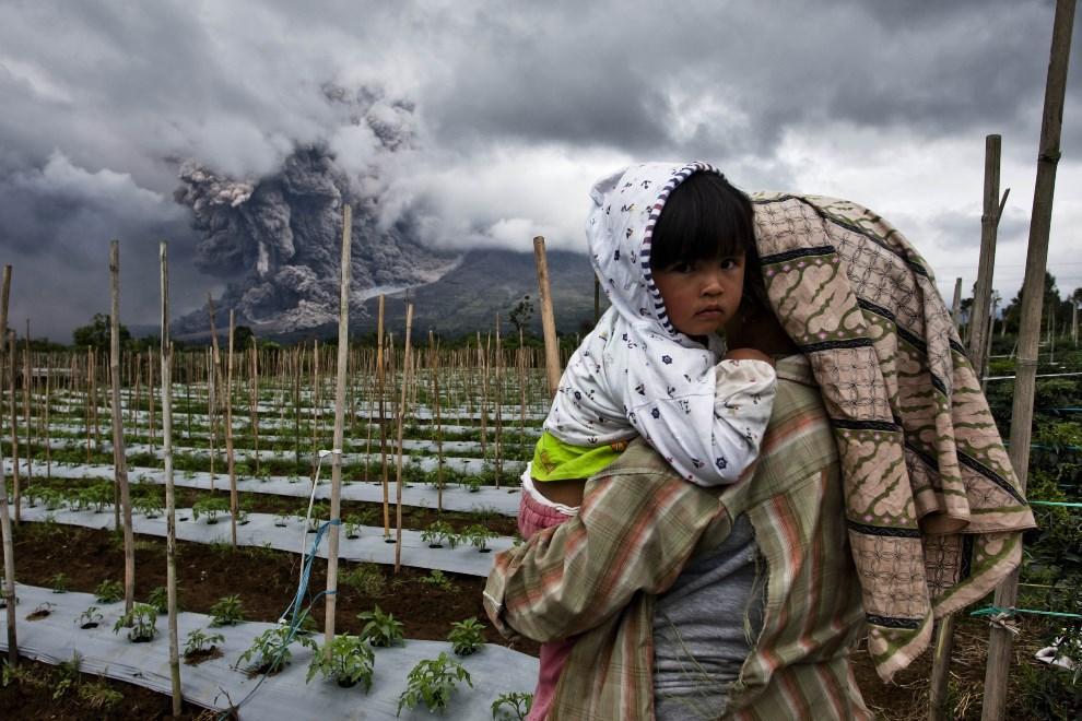 21.INDONEZJA, Simpang Empat, 4 stycznia 2014: Kobieta z dzieckiem na rękach przygląda się erupcji wulkanu. (Foto: Ulet Ifansasti/Getty Images)