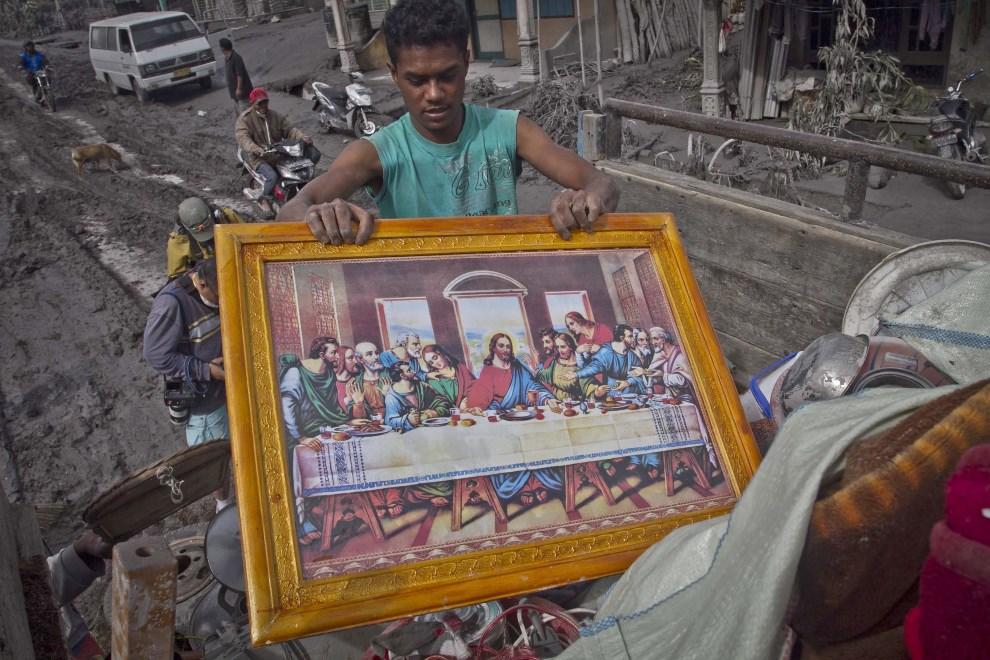 21.INDONEZJA, Namanteran, 12 stycznia 2014: Mężczyzna ładuje na ciężarówkę rzeczy uratowane ze zniszczonego domu. EPA/ADE SAHPUTRA Dostawca: PAP/EPA.