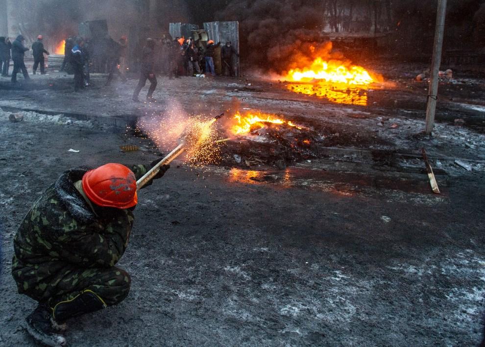 22.UKRAINA, Kijów, 22 stycznia 2014: Protestujący odpala racę w kierunku milicji. AFP PHOTO/ VOLODYMYR SHUVAYEV