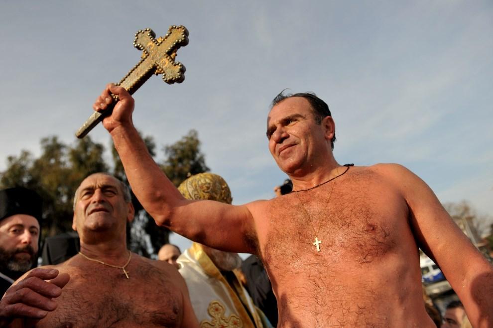 23.TURCJA, Stambuł, 6 stycznia 2014: Mężczyzna, trzyma krzyż wyłowiony z Bosforu. AFP PHOTO/OZAN KOSE