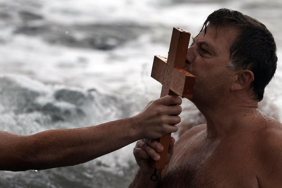 24.GRECJA, Atena, 6 stycznia 2014: Mężczyzna całujący krzyż podczas błogosławieństwa. AFP PHOTO / ARIS MESSINIS