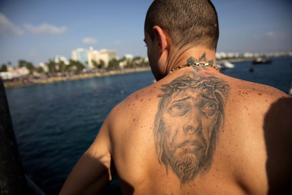 26.CYPR, Limassol, 6 stycznia 2014: Mężczyzna z wytatuowanym wizerunkiem Chrystusa przygotowuje się do skoku do morza. AFP PHOTO / YIANNIS KOURTOGLOU