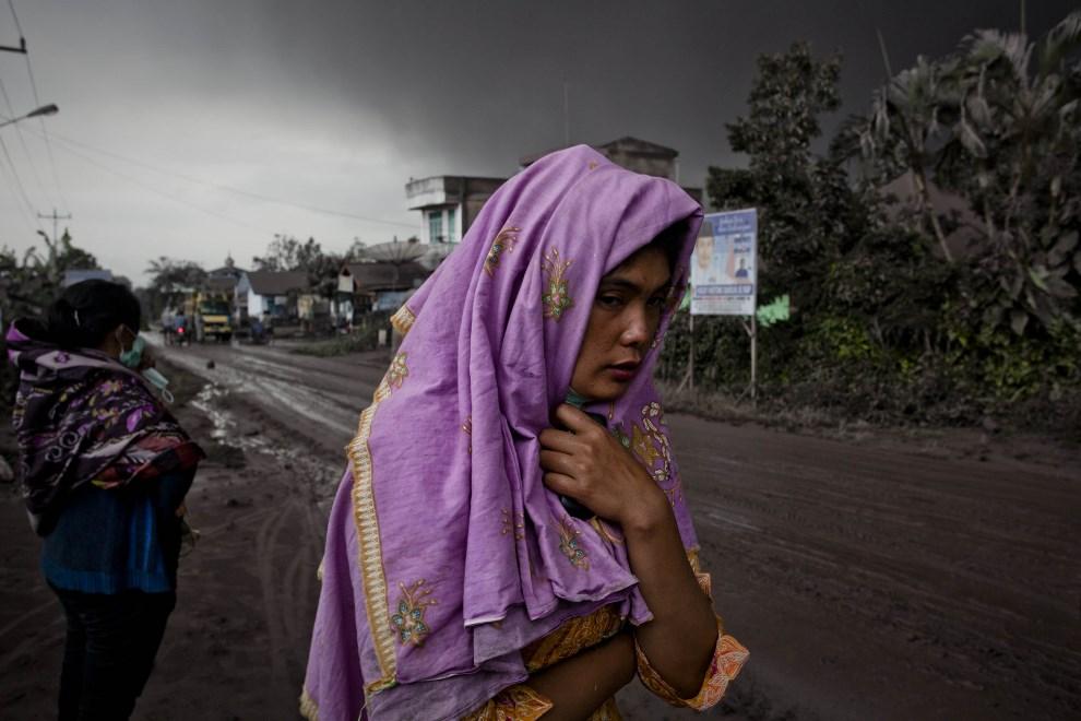 25.INDONEZJA, Tiga Pancur, 4 stycznia 2014: Kobieta na drodze pokrytej pyłem wulkanicznym i błotem. (Foto: Ulet Ifansasti/Getty Images)