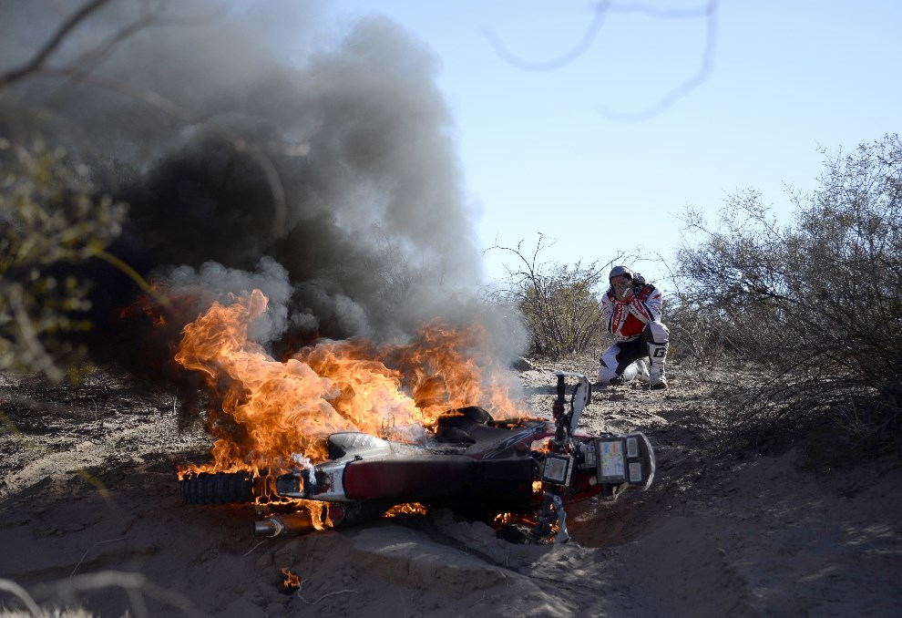 26.ARGENTYNA, Tucumán, 9 stycznia 2014: Paulo Goncalves przygląda się swojemu płonącemu motocyklowi. AFP PHOTO / FRANCK FIFE