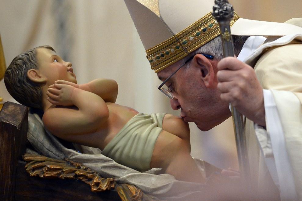 27.WATYKAN, 6 stycznia 2014: Papież Franciszek całuje statuetkę przedstawiającą narodzonego Chrystusa. AFP PHOTO / VINCENZO PINTO