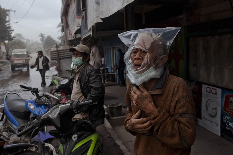 27.INDONEZJA, Payung, 8 stycznia 2014: Mężczyzna w plastikowym worku chroniącym go przed opadającym pyłem wulkanicznym. (Foto: Ulet Ifansasti/Getty Images)