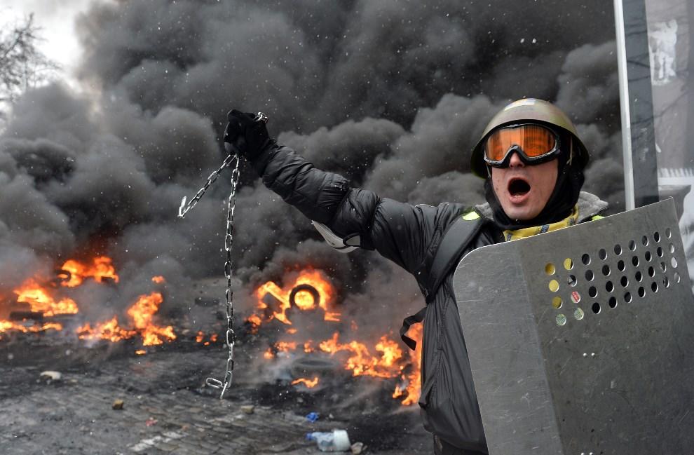 27.UKRAINA, Kijów, 22 stycznia 2014: Protestujący z łańcuchem, stoi na barykadzie. AFP PHOTO / SERGEI SUPINSKY