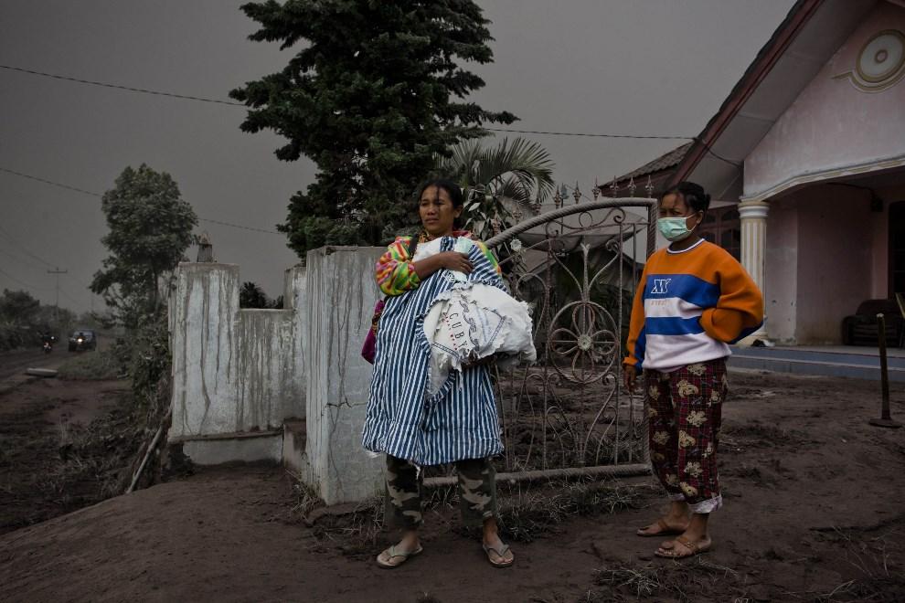 26.INDONEZJA, Tiga Pancur, 4 stycznia 2014: Kobieta z dzieckiem czeka na ewakuację z zagrożonego obszaru. (Foto: Ulet Ifansasti/Getty Images)
