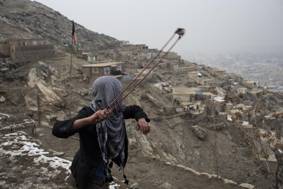 2.AFGANISTAN, Kabul, 13 stycznia 2014: Chłopak z procą na wzgórzu ponad Kabulem.  AFP PHOTO/JOHANNES EISELE