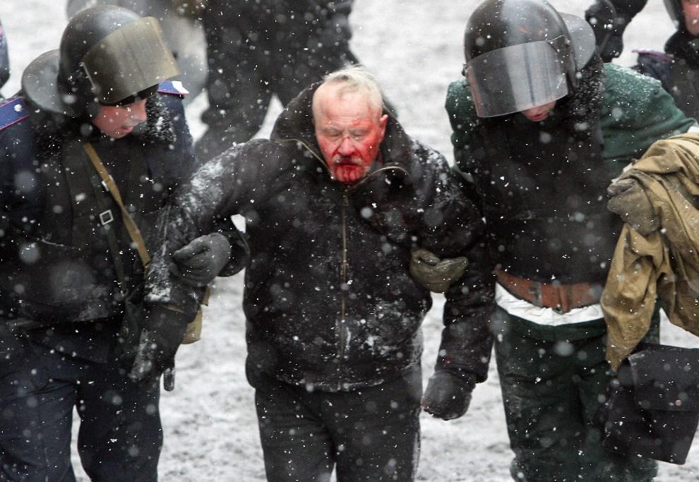 30.UKRAINA, Kijów, 22 stycznia 2014: Milicjanci odprowadzają rannego uczestnika walk. AFP PHOTO/ ANATOLII BOIKO