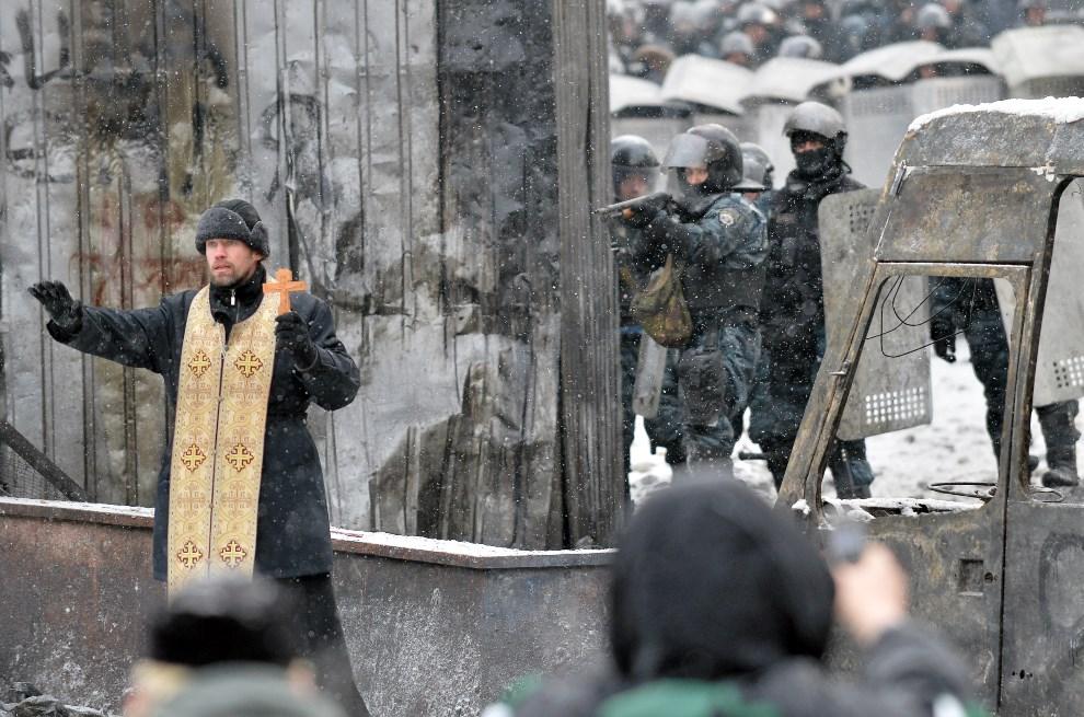 31.UKRAINA, Kijów, 22 stycznia 2014: Prawosławny duchowny stara się powstrzymać walczące ze sobą strony. AFP PHOTO/ SERGEI SUPINSKY