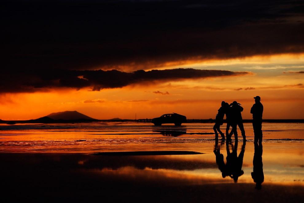 36.BOLIWIA, Uyuni, 11 stycznia 2014: Turyści podziwiają zachód słońca na solnisku Salar de Uyuni. (Foto: Dean Mouhtaropoulos/Getty Images)