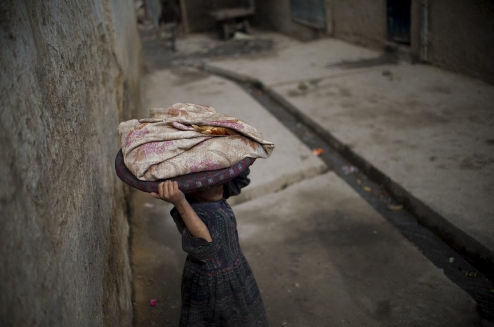 3.AFGANISTAN, Kabul, 16 stycznia 2014: Dziewczyna niosąca pieczywo. AFP PHOTO/JOHANNES EISELE