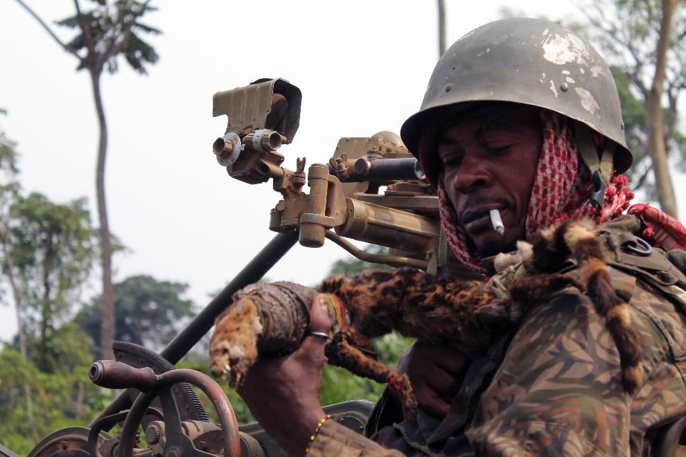 3.DEMOKRATYCZNA REPUBLIKA KONGA, Kokola (brak dokładnej daty): Żołnierz oddziałów rządowych pokazuje swoją fretkę – talizman. AFP PHOTO / ALAIN WANDIMOYI