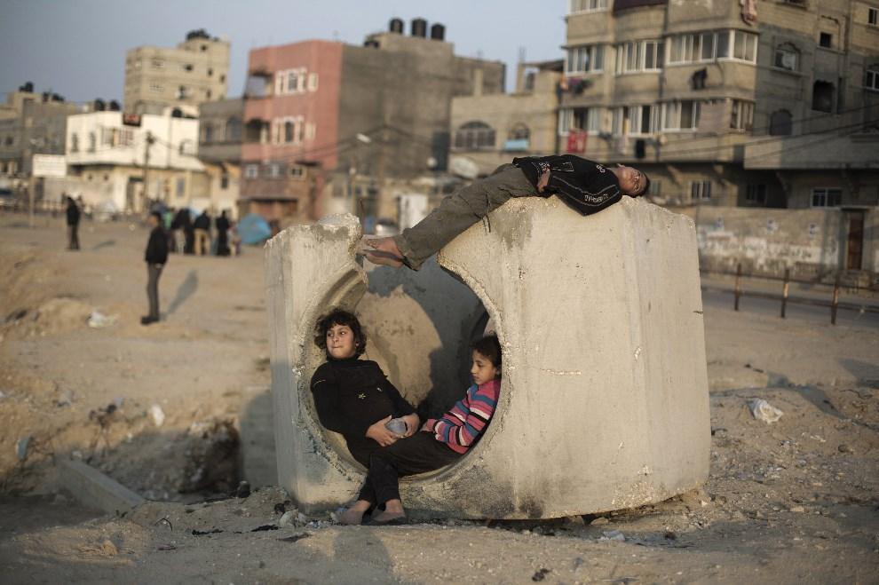 4.STREFA GAZY, 15 stycznia 2014: Palestyńskie dzieci bawią się na ulicy. AFP PHOTO/MOHAMMED ABED