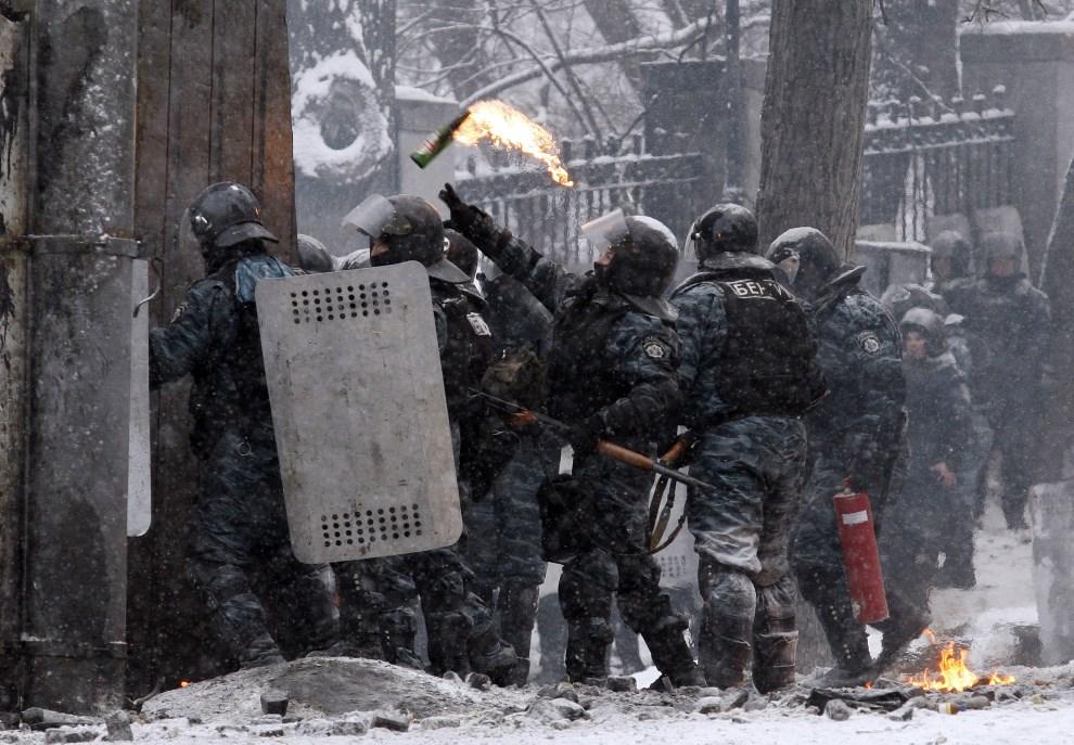 5.UKRAINA, Kijów, 22 stycznia 2014: Milicjant rzuca butelką z koktajlem Mołotowa. AFP PHOTO/ YURIY KIRNICHNY
