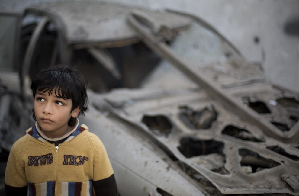5.STREFA GAZY, 16 stycznia 2014: Palestyńczyk przy samochodzie zniszczonym podczas nocnego nalotu. AFP PHOTO/MOHAMMED ABED