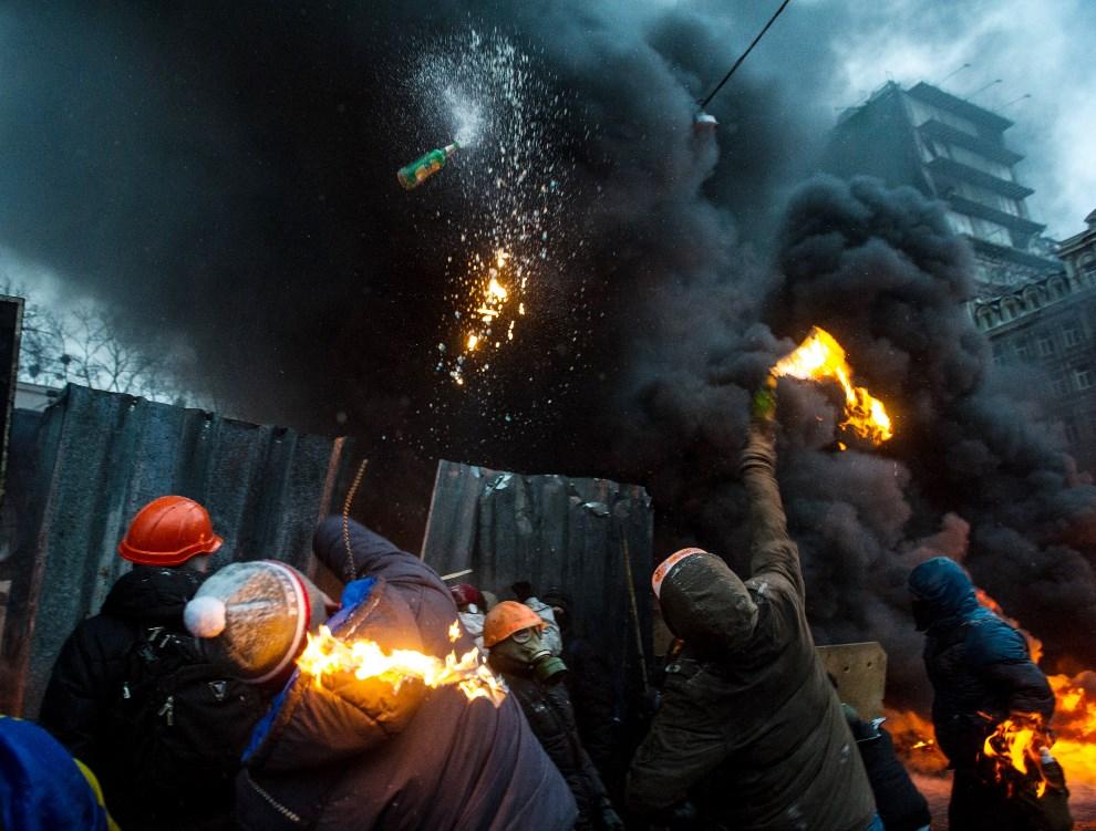 6.UKRAINA, Kijów, 22 stycznia 2014: Protestujący rzucają butelkami z koktajlem Mołotowa. AFP PHOTO/ VOLODYMYR SHUVAYEV