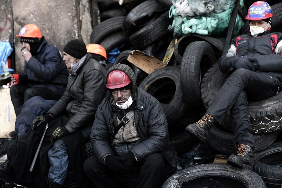 6.UKRAINA, Kijów, 26 stycznia 2014: Protestujący odpoczywają na barykadzie z opon. AFP PHOTO / ARIS MESSINIS