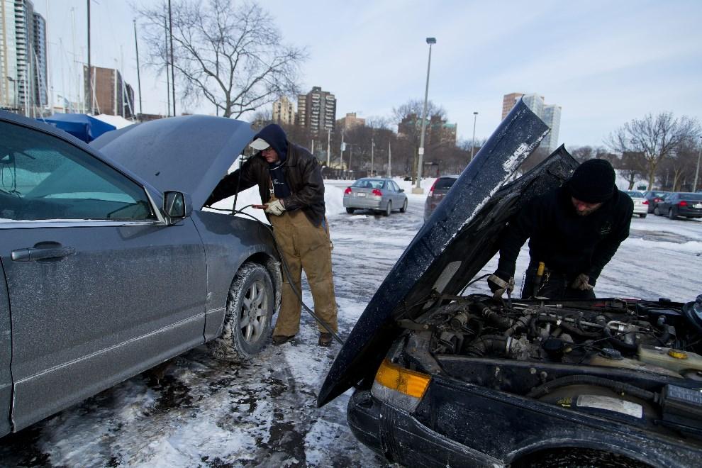 6.USA, Milwaukee, 7 stycznia 2014: Travis Olesak (po prawej) pomaga odpalić samochód Dana Couillarda. (Foto: Darren Hauck/Getty Images)