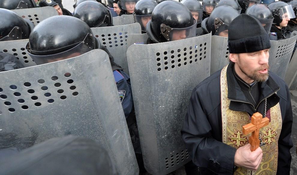 7.UKRAINA, Kijów, 14 stycznia 2014: Kapłan stojący przed szeregiem oddziału policji. AFP PHOTO/ SERGEI SUPINSKY